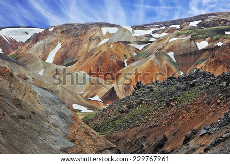 National Park Landmannalaugar in Iceland. Pieces of gray and black lava, sometimes covered with green moss. In the background - orange rhyolite mountains with last year's snow in the hollows - stock photo