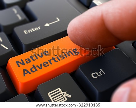 Native Advertising Button. Male Finger Clicks on Orange Button on Black Keyboard. Closeup View. Blurred Background. - stock photo