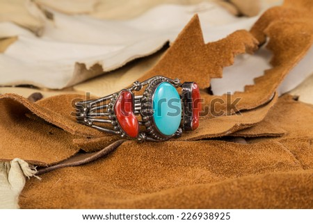 Native American Bracelet of Turquoise and Coral set in Sterling Silver against scrap pieces of suede and buckskin leather. - stock photo