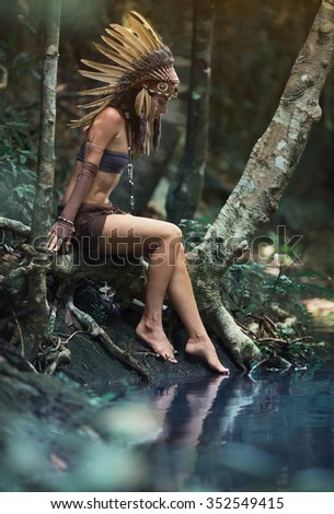 Native american, Indian woman in traditional dress,pensively looking in the pond - stock photo