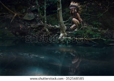 Native american,indian woman in traditional dress,pensively looking in the pond with big fish inside - stock photo