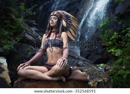 Native american, Indian woman in traditional dress,posing in the wild forest,meditation with waterfall on backgraound - stock photo