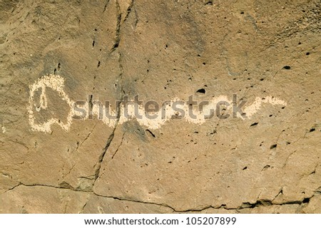 Native American petroglyphs featuring an image of a snake at Petroglyph National Monument, outside Albuquerque, New Mexico - stock photo