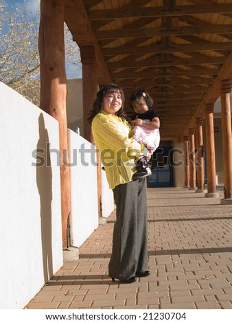 Native American woman & daughter in afternoon sun under a canopied walkway - stock photo