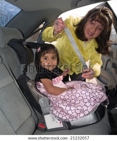 Native American woman placing her daughter in a child safety seat and fastening her seat belt - stock photo
