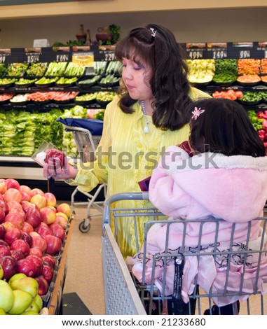 Native American woman shopping in the produce department of a grocery store - stock photo