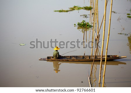 Native Asian fisherman sitting on the boat with bamboo - stock photo