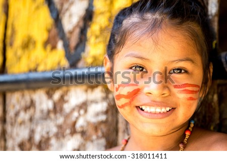 Native Brazilian girl smiling at an indigenous tribe in the Amazon - stock photo