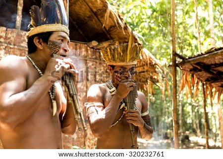 Native Brazilian men playing wooden flute at an indigenous tribe in the Amazon - stock photo