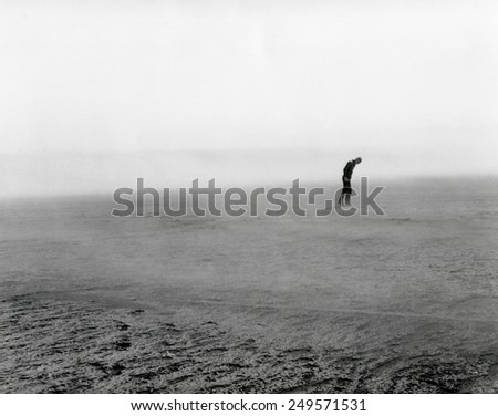 Native pasture land blowing in Dixon, South Dakota, May 1936. Figure in the distance in bent forward to resist the force of the wind. - stock photo