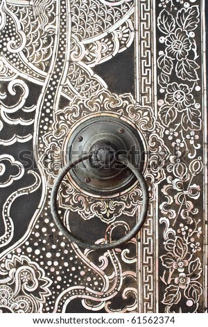 Native Thai style wood carving on door at temple - stock photo