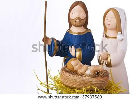 Nativity scene: Jesus, Mary and Joseph at the manger. Focus on baby Jesus, soft focus on Mary and joseph. - stock photo