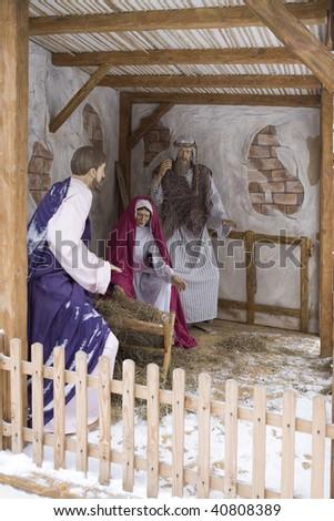 Nativity scene: Jesus, Mary and Joseph at the manger. Snow`s street near church - stock photo