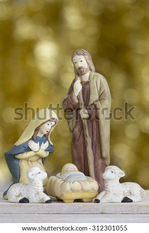 Nativity Scene with Baby Jesus, Mary, Joseph, and Sheep on a Golden Background with Copy Space - Vertical  - stock photo