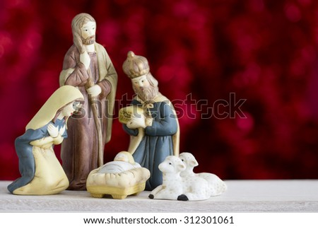 Nativity Scene with Baby Jesus, Mary, Joseph, Sheep and a Wise Man on a Red Background with Copy Space  - stock photo