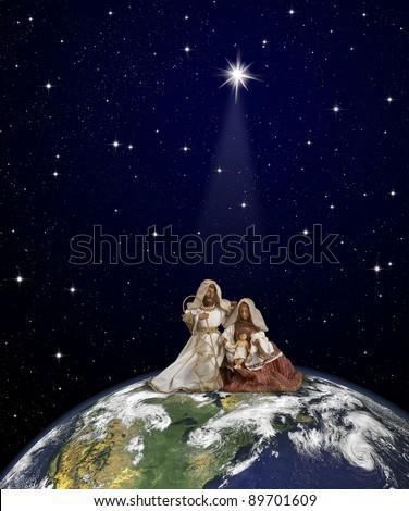 Nativity scene with Jesus, Maria and Joseph  at  globe top on space background under Christmas star beam. World map courtesy of NASA. - stock photo