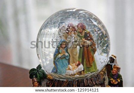 Nativity with Joseph Mary and baby Jesus in a sphere of water with snow falling - stock photo