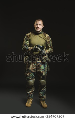 NATO soldier in full gear. Military man over black background. - stock photo