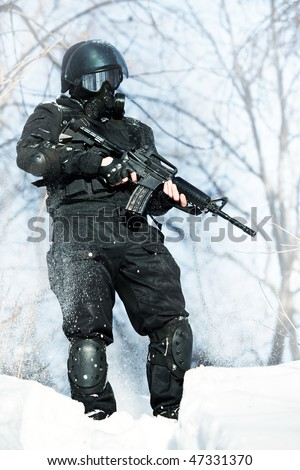 NATO soldier in winter uniform with the M4 machine gun on the forest background. - stock photo