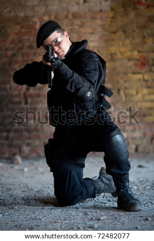 NATO soldier with M4 rifle on the brick wall background. - stock photo