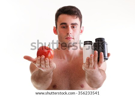 natural apple vitamin or pill drag tablet. Man isolated offering fruit in one and pills in bottle - in another hand. Copy space boxes with supplements