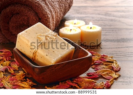 Natural artisan made Marseilles type aromatherapy and body care bath soap bar in a wood dish with towel and burning candles for a pampering cleansing session in a relaxation spa - stock photo