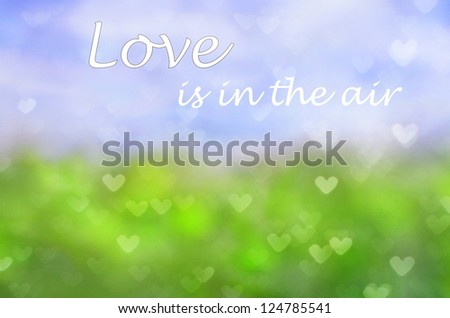 natural background with grass and sky with a layer of little hearts and the words written in the sky ; Love is in the air