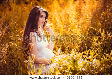 Natural Beautiful pregnant woman relaxing and enjoying life in the field at sunset.