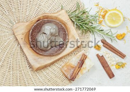 Natural beauty care. Spa still life with  natural ingredients: spa mud, lemon, dried calendula flowers, handmade cinnamon pumpkin soap and oat . Macro photograph, selective focus  - stock photo