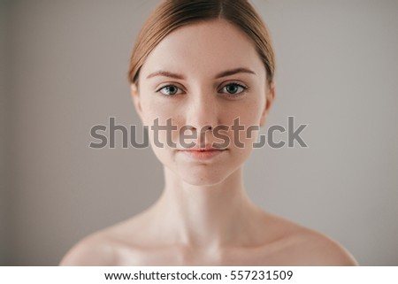 Natural beauty. Portrait of redhead woman with freckles looking at camera while standing against grey background