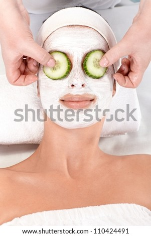 Natural beauty treatment with facial mask and cucumber. - stock photo