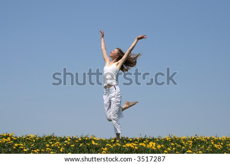 Natural beauty. Young woman in summer white clothes dancing in a flowering field. - stock photo