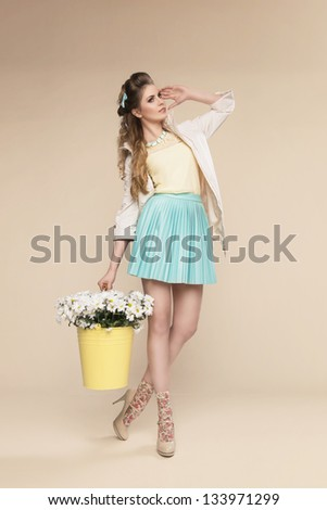 Natural blonde beauty posing with basket full of flowers on beige background - stock photo