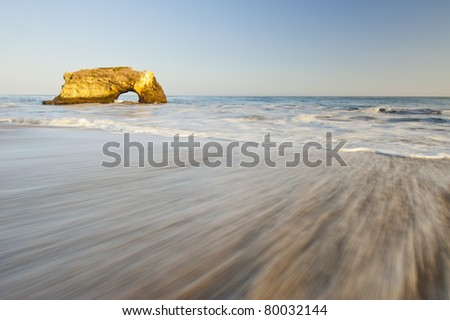 Natural Bridges rock in the Beach of Santa Cruz, California, USA. With ocean wave in the foreground. - stock photo