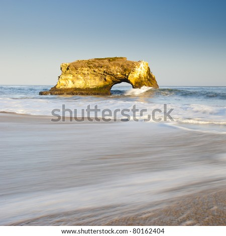 Natural Bridges rock in the Beach of Santa Cruz, California, USA. With ocean wave in the foreground - stock photo