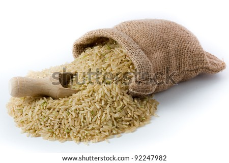 Natural brown rice in small burlap sack and wooden spoon - stock photo