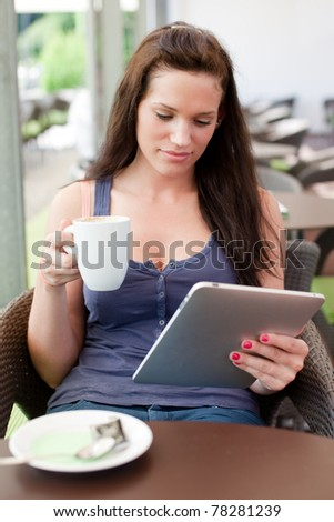 Natural/candid young woman having a cup of coffee/tea while reading an article on her tablet