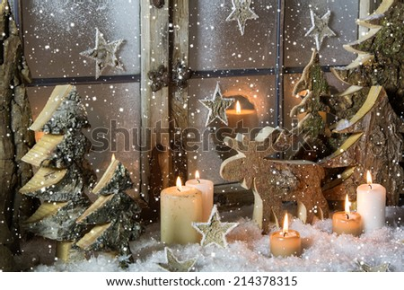 Natural christmas window decoration with handmade reindeer and trees of wood. - stock photo