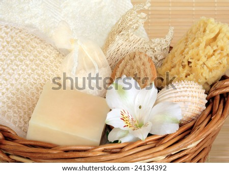 Natural cleansing products in a wicker basket including a cream flannel, soap, sponges, exfoliating sisal pad, hand brush, vanilla bath salts in a net bag and a white lily flower. - stock photo
