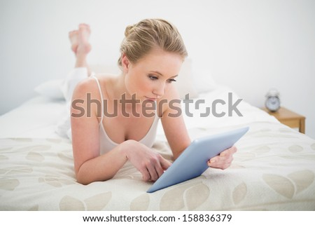 Natural content blonde lying on bed using tablet in bright bedroom - stock photo