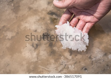 Natural crystal salt piles on hand from Samutsakorn, Thailand