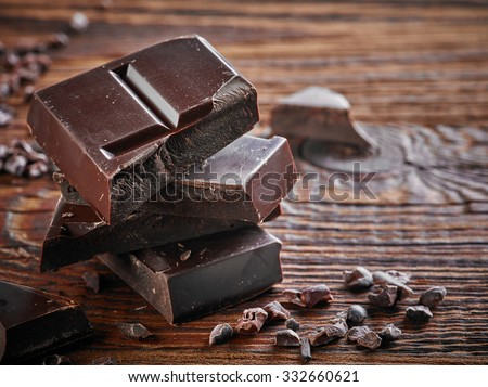 Natural dark chocolate pieces on wooden table - stock photo
