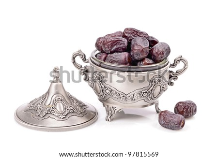 Natural dates in a metal container, isolated white background - stock photo