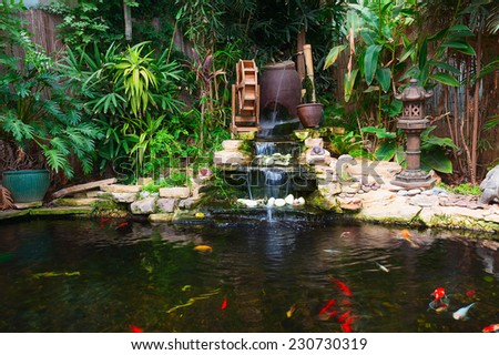 Natural decorative pond with fountain and gold fish - stock photo