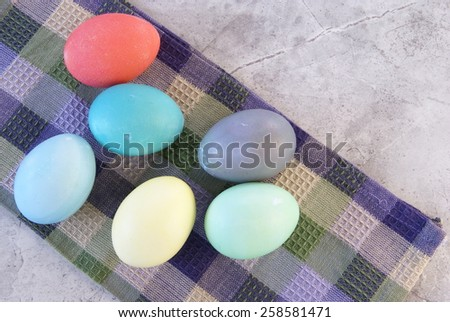 Natural dyed Easter eggs are laying out to dry on a towel on a marble surface.