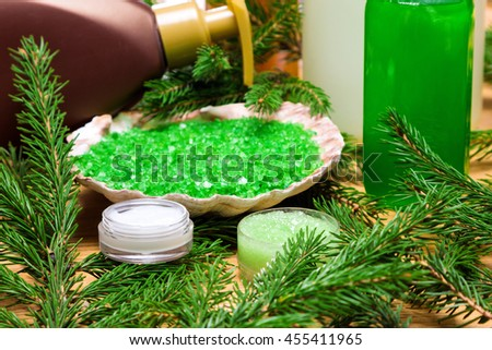 Natural facial skincare products: moisturizing eye cream, organic honey and herbal scrub, sea salt with essential oils, facial wash gel, liquid soap surrounded by firry branches on wooden surface - stock photo