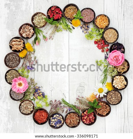 Natural flower and herb selection used in herbal medicine in bowls and loose forming a circle over distressed wooden background. - stock photo