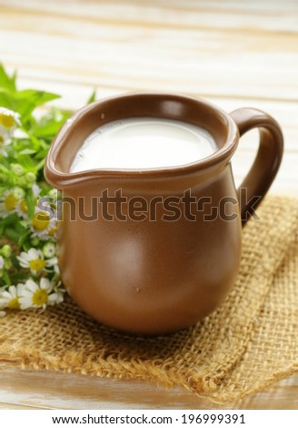 natural fresh milk in a ceramic jug on a wooden table - stock photo