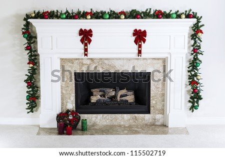Natural Gas Fireplace decorated with Christmas ornaments, candles and basket of dried pine cones for the holiday season - stock photo
