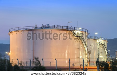 Natural Gas storage tanks and oil tank in industrial plant at twilight - stock photo